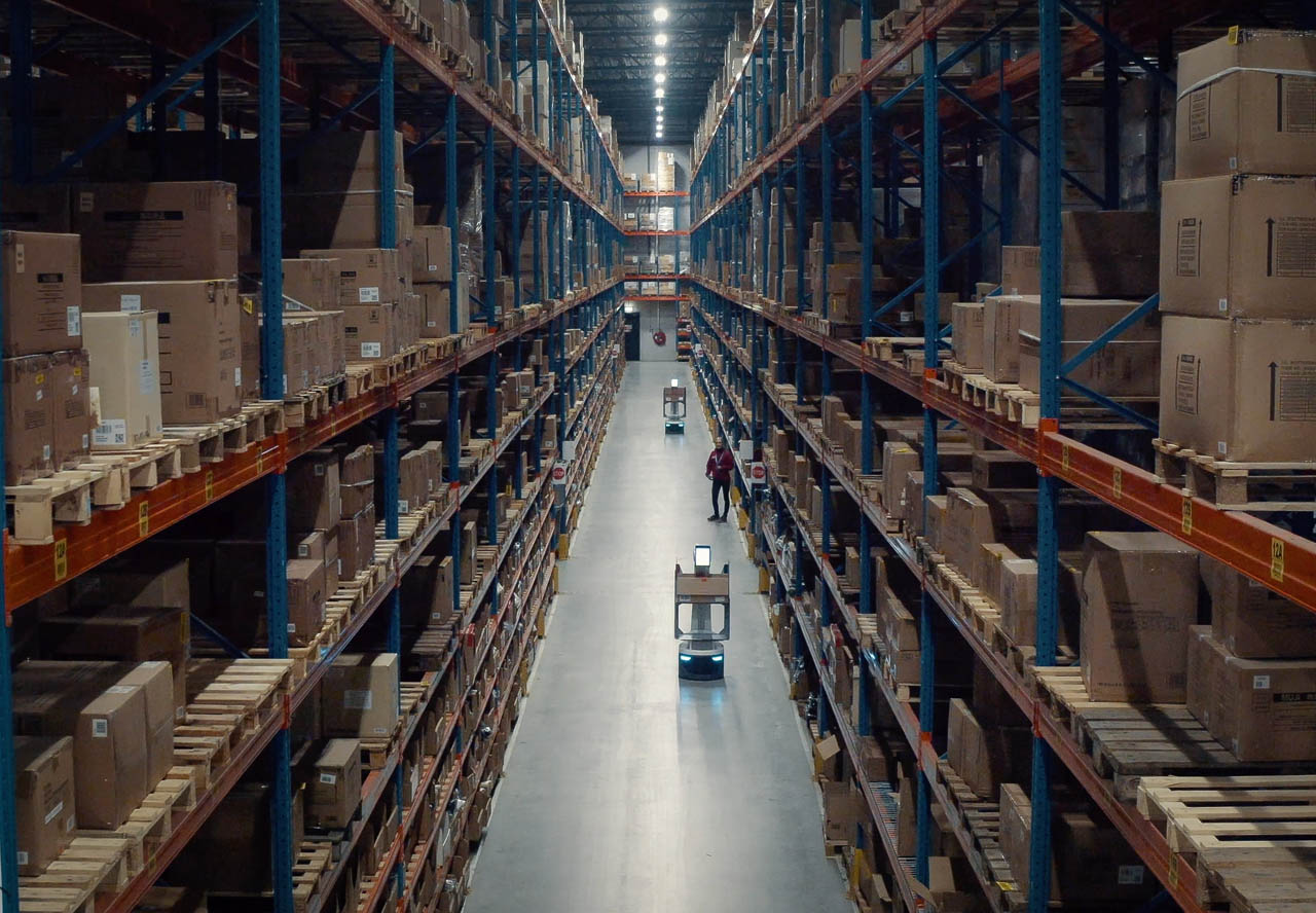 LocusBots in warehouse aisle with Aila scanning
